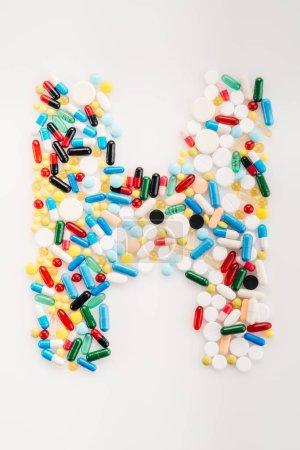 Photo pour Vue du dessus de la lettre H fabriquée à partir de pilules et capsules médicales, concept de médecine et de soins de santé - image libre de droit