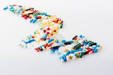 Photo pour Vue rapprochée de la flèche en pilules médicales sur blanc - image libre de droit