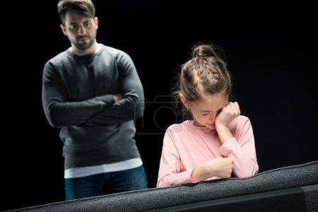 Photo pour Père bouleversé avec les bras croisés regardant pleurer fille isolée sur noir, concept de problèmes familiaux - image libre de droit