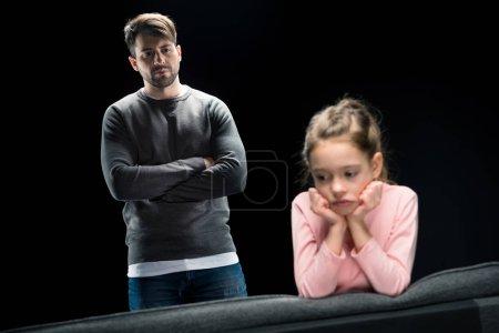 Photo pour Père sérieux avec les bras croisés regardant bouleversé petite fille isolée sur noir, concept de problèmes familiaux - image libre de droit