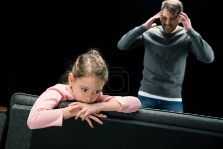 Photo pour Aggressive father standing near upset daughter sitting on couch isolated on black, family problems concept - image libre de droit