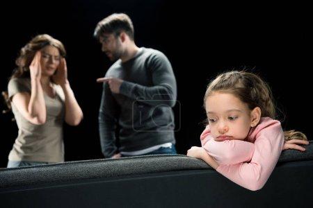 Photo pour Petite fille bouleversée assise sur le canapé pendant que les parents se querellent isolés sur le concept de problèmes familiaux noirs - image libre de droit