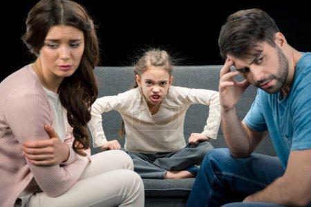 Photo pour Portrait de fille en colère et parents bouleversés isolés sur noir, concept de problèmes familiaux - image libre de droit