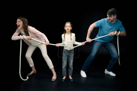 Photo for Parents pulling over shocked daughter with rope isolated on black, divorce and separation concept - Royalty Free Image