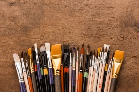 Photo for Close-up top view of various paintbrushes collection on brown wooden table - Royalty Free Image
