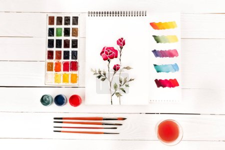 Photo pour Vue du dessus du dessin de fleurs, peintures et pinceaux sur table en bois, concept printemps - image libre de droit