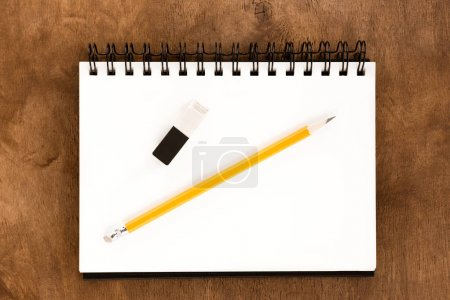 Photo for Top view of pencil, drawing album and eraser on wooden table - Royalty Free Image
