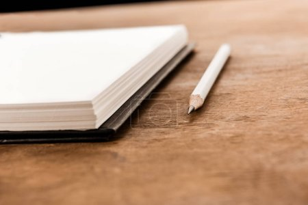 Photo for Close-up view of pencil and empty notebook on wooden table - Royalty Free Image