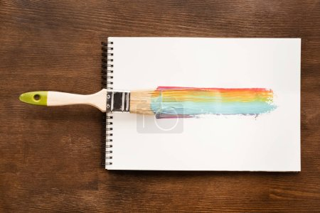 Photo for Top view of brush and colorful brushstroke on paper on table - Royalty Free Image