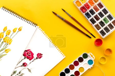 Photo for Top view of drawings of flowers, paints and brushes on yellow, springtime concept - Royalty Free Image