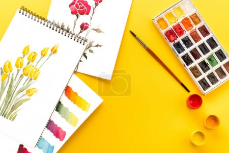 Photo for Top view of drawings of flowers, paints, brush and colorful brushstrokes on paper on yellow, springtime concept - Royalty Free Image