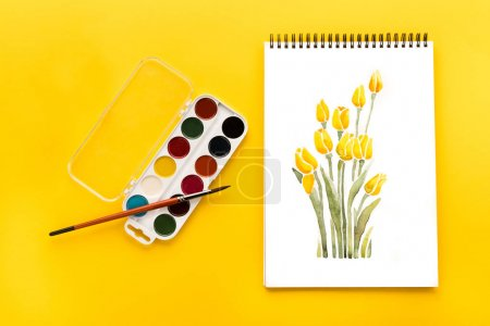 Photo for Top view of drawing of flowers, paints and brush on yellow, springtime concept - Royalty Free Image