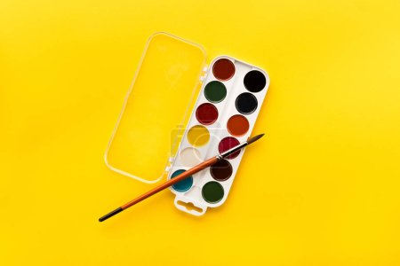 Photo for Top view of brush and paints on yellow - Royalty Free Image