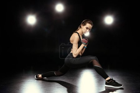 Photo for Sportswoman doing stretching exercises on black - Royalty Free Image