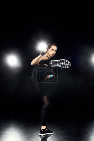 Photo for Attractive sportswoman training and kicking on black - Royalty Free Image