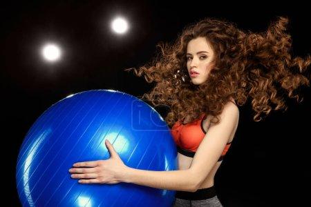 sportswoman holding fitness ball