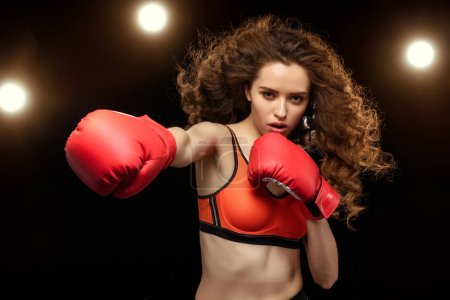 Photo for Sportswoman boxer training and punching on black - Royalty Free Image
