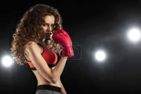 Photo pour Vue latérale d'une jeune femme sérieuse avec des cheveux bouclés en gant de boxe - image libre de droit