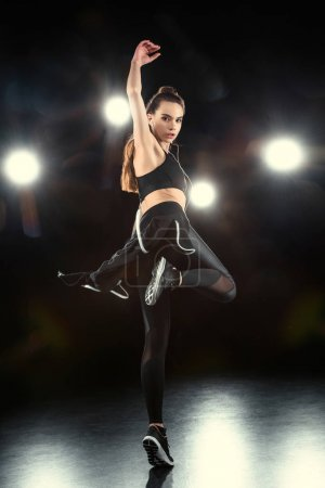 Photo for Woman dancing in sportive clothing on black - Royalty Free Image