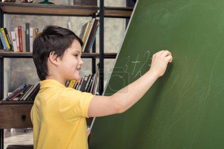 Photo pour Vue de côté d'écolier souriant écrit sur le tableau noir - image libre de droit