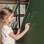 Side view of smiling schoolgirl writing on chalkbo...