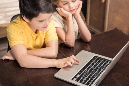 Photo pour Mignon garçon et fille assis à la table en bois et en utilisant un ordinateur portable - image libre de droit