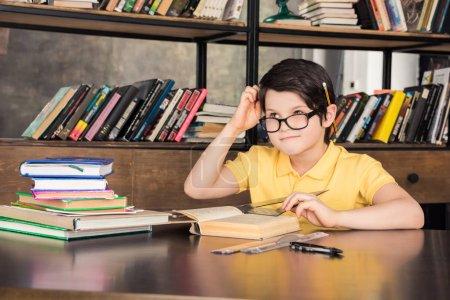 Photo pour Lycéen en lunettes assis à table avec des livres et d'étudier dans la bibliothèque - image libre de droit