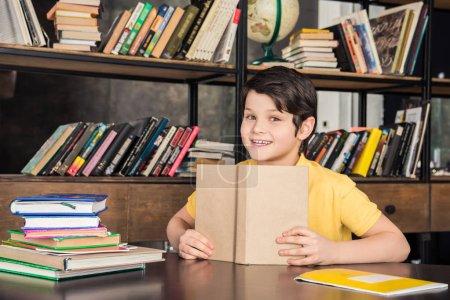 Photo pour Livre de tenue mignonne écolier en bibliothéconomie et en souriant à la caméra - image libre de droit