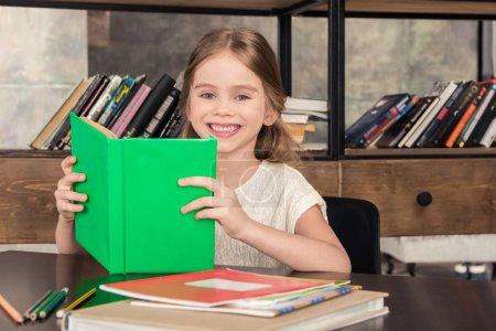 Photo pour Petite écolière mignonne tenant le livre et souriant à la caméra - image libre de droit