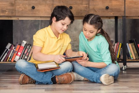 Photo for Boy teaching focused girl how to use digital tablets in library - Royalty Free Image