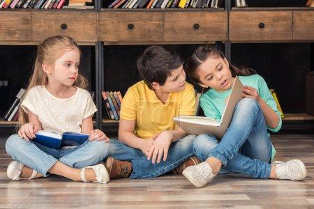 Photo pour Garçons et filles lisant des livres à la bibliothèque - image libre de droit