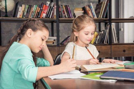 Photo pour Vue de côté de camarades de classe concentrés à faire leurs devoirs ensemble dans la bibliothèque - image libre de droit