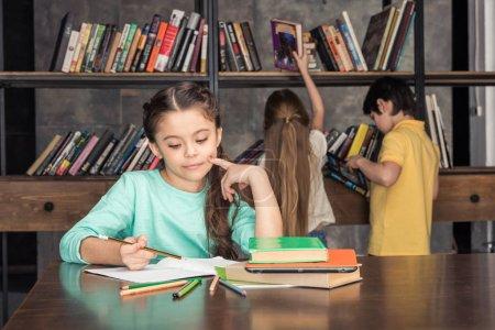 Photo pour Portrait de fille songeuse à faire leurs devoirs avec ses camarades de classe à la recherche de livres derrière - image libre de droit
