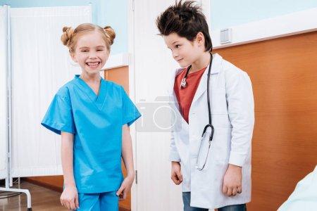 Foto de Médico de niño mirando riendo enfermera niña en sala de hospital - Imagen libre de derechos