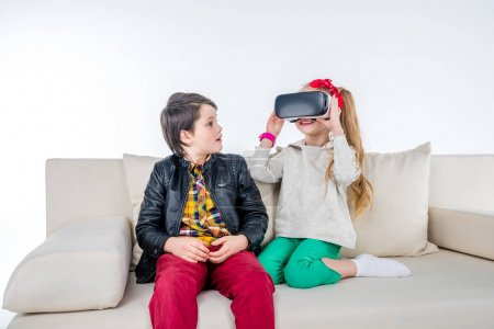 Photo for Children with Virtual reality headset sitting on sofa isolated on white - Royalty Free Image