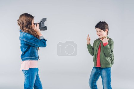Girl taking pictures of boy