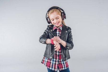 Photo pour Souriante fille dans les écouteurs vérifier smartwatch isolé sur gris - image libre de droit