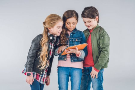 Photo for Three cute little kids using digital tablet together isolated on grey - Royalty Free Image
