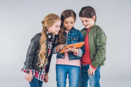Photo pour Trois mignons petits enfants utilisant la tablette numérique ensemble isolé sur gris - image libre de droit