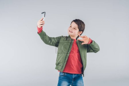 Foto de Cute smiling boy taking selfie with smartphone and gesturing  isolated on grey - Imagen libre de derechos