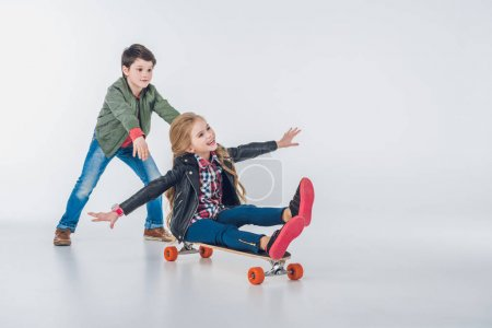 Foto de Happy boy and girl having fun with skateboard isolated on grey - Imagen libre de derechos