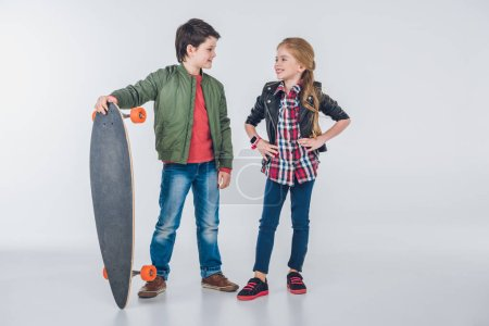 Photo for Confident smiling boy and girl standing with skateboard and looking at each other isolated on grey - Royalty Free Image