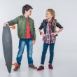 Confident smiling boy and girl standing with skate...