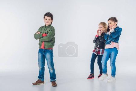 Photo pour Deux filles riantes se moquent du garçon debout avec les bras croisés isolés sur gris - image libre de droit
