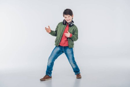 Foto de Cute little boy with headphones smiling and having fun isolated on grey - Imagen libre de derechos