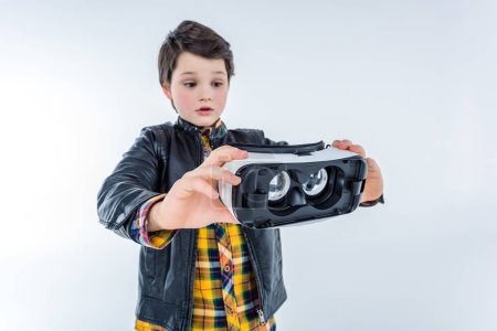 Photo for Portrait of confused boy holding virtual reality headset  isolated on grey - Royalty Free Image