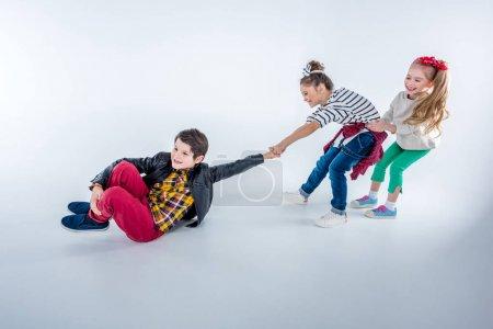 Photo pour Vue latérale des filles riantes tirant vers le haut garçon isolé sur gris - image libre de droit