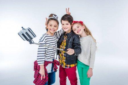 Photo pour Vue latérale de garçons et de filles souriants faisant selfie isolé sur gris - image libre de droit