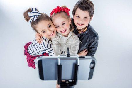 Photo pour Vue grand angle de sourire garçon et filles faisant selfie isolé sur gris - image libre de droit