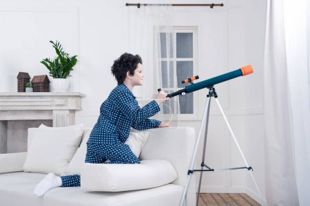 little boy looking through telescope
